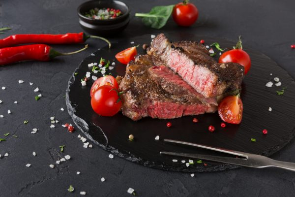 Rare rib eye steak on dark plate decorated with tomatoes, chilli, spices and meat fork, closeup